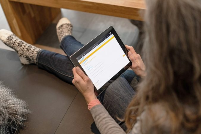 Zu sehen ist eine Frau mit Tablet, die auf die Internetseite des Online-Tools zur BAFA-Förderung der VdZ schaut. Digitale Kommunikation betirfft auch die Förderung der Solarthermie.