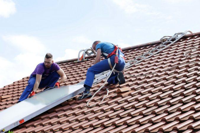 Zu sehen sind Installateure auf einem dach mit Sonnenkollektor. Die Solarthermie Förderung führt zu vermehrten Installationen.