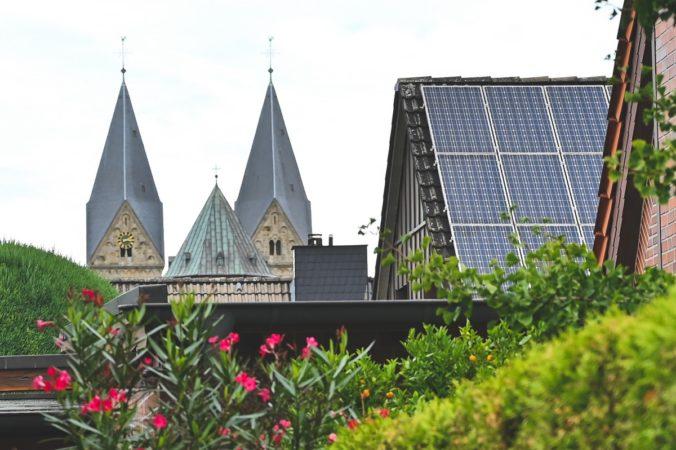 Solarförderung in Neuenkirchen: Zu sehen ist sind die Kirchtürme der Pfarrkirche St. Anna und eine PV-Anlage.