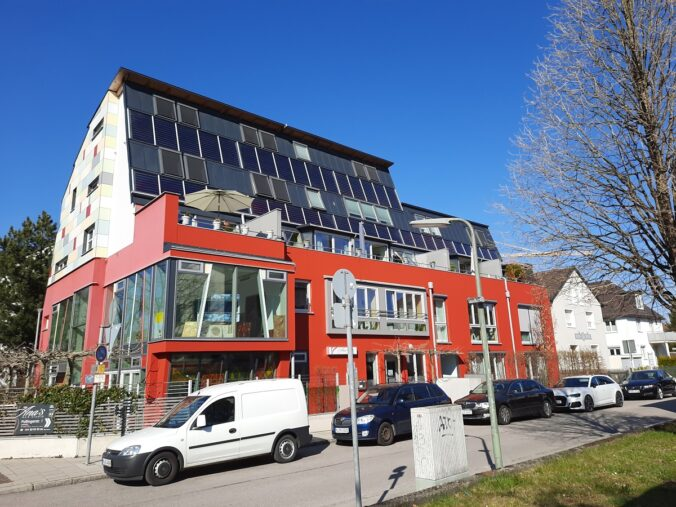 Zu sehen ist ein Wohn- und Geschäftshaus in München, dessen Solarthermie-Anlage von der BEG-Förderung profitierne könnte, wenn sie dieses Jahr errichtet würde.
