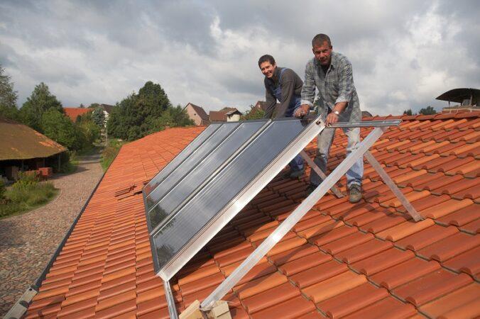 Zu sehen sind zwei Männer, die eine Solarthermie-Anlage installieren, solche Solaranlagen erhalten in Essen ab 2022 eine Förderung.